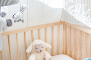 A neutral crib with a stuffed animal in it.