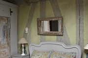 Rectangle mirror above vintage headboard.