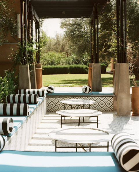 Outdoor Bench Seating - A poolside outdoor lounge area with striped pillows