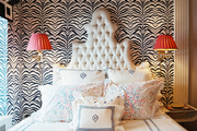 A white tufted headboard and sconces with pink shades against zebra-print wallpaper