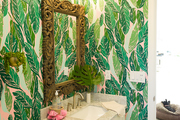 A bathroom with pink and green wallpaper.