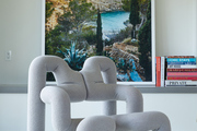 A sculptural arm chair sits in front of a framed print.
