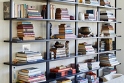 A filled open bookcase with books and decor.