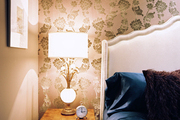 Floral wallpaper paired with a vintage lamp and a white upholstered headboard