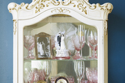 A display cabinet with wedding china, kitchen valuables, and picture frames inside.