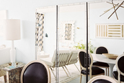 A dining space decorated with a trio of mirrors