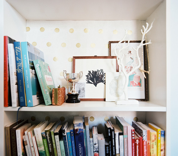 Polka Dot - A white bookshelf backed with polka-dot paper
