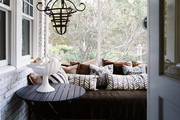 A daybed covered with patterned pillows and an iron chandelier on a porch