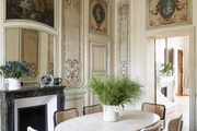 Decorative walls surrounding a dining room with a marble table, a marble fireplace, and floral arrangements.