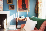 An upholstered chaise in a living space with blue walls and floral curtains