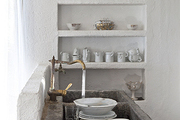 A stone sink and brass faucet in the kitchen of a Spanish artist's cottage.