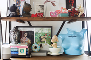 A detail of eclectic shelving with various kitschy decor items and books.