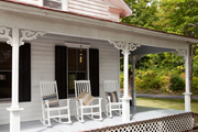 A wraparound porch with beautifully detailed beams