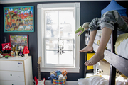A boy's room with chalkboard walls, a bunk bed, and bright artwork