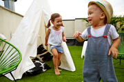Poppy and Rhys Edwards with a tepee and Baby Acapulco Chairs on their rooftop patio, covered with synthetic lawn