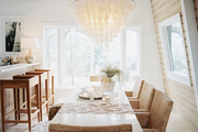 A capiz-shell chandelier above a white dining table