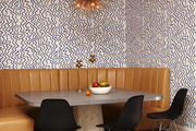 Bright patterned walls surrounding diner-style seating and modern black chairs.