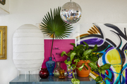 A disco ball hanging above a bedroom dresser with plants and colorful vases.