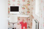 Floral wallpaper paired with a white modern desk and a molded-plastic chair