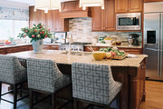 Wooden cabinetry and blue barstools in a kitchen
