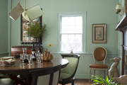 A pendant lamp above an oval dining table and curved chairs in a Hamptons dining room