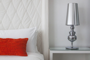 A white wingback headboard in a guest suite