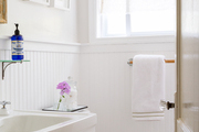 A sun-filled bathroom with wainscoting detail