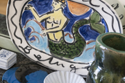 A mermaid printed serving tray sitting on top of a shelf in a dining room.