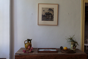 A wooden drop-leaf table below a framed piece of art