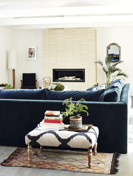 Rachel Bilson - A bone-color brick veneer fireplace set behind a blue velvet sofa and printed ottoman