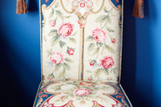 A dining chair covered with a tapestry