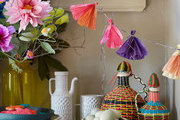 Paper tassels and paper flowers decorate a  festive sideboard