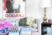 A gray couch with patterned throw pillows beneath an art poster