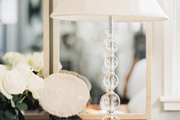 A crystal table lamp on a wooden bedside table