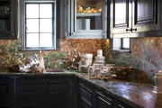 Marble countertops and gray cabinets in a butler's pantry