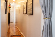 A long, narrow hallway is brightened with a string of hanging lights