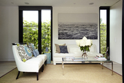 Tall windows behind white couches and seagrass rug.