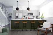 A contemporary kitchen with a green and white kitchen counter.