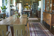 This dining area features a vintage runner, blue walls, and a vintage table and chairs.