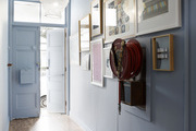 This hallway is painted blue and decorated with a gallery wall and a vintage fire hose.