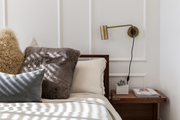 Swing-arm bedside light above wood nightstand and white bedding.