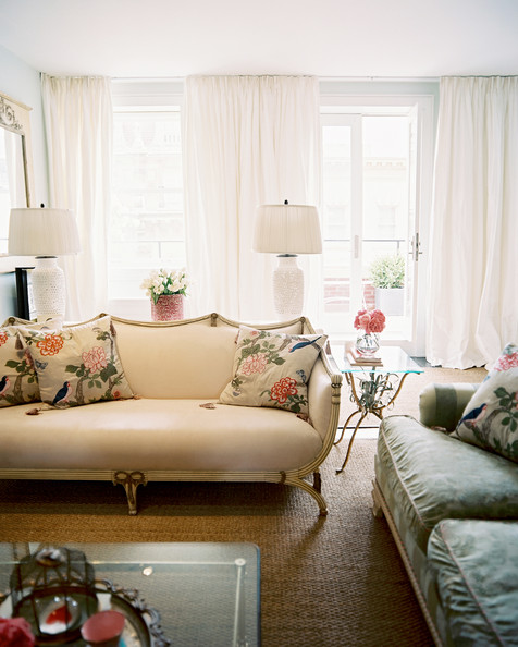 Settee - A pair of white lamps behind a beige settee with floral pillows