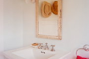 An antique mirror hangs above a pedestal sink in a shabby chic bathroom.