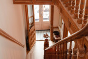 A Browntone entry way with original carved-wood detailing on the stair railing.
