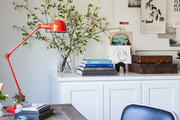 Eclectic decor atop wooden desk and cabinet.