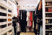 White built-in shelving and a natural-fiber rug in a walk-in closet