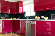 A contemporary kitchen with red cabinets.