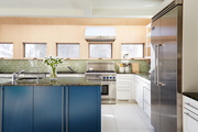 Contemporary green, peach, and blue kitchen with stainless steel appliances.