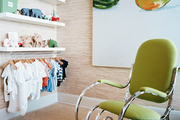A green rocking chair and zebra-print rug in a nursery