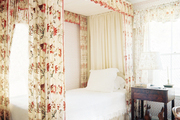 A floral-print canopy and white bedding atop a striped rug